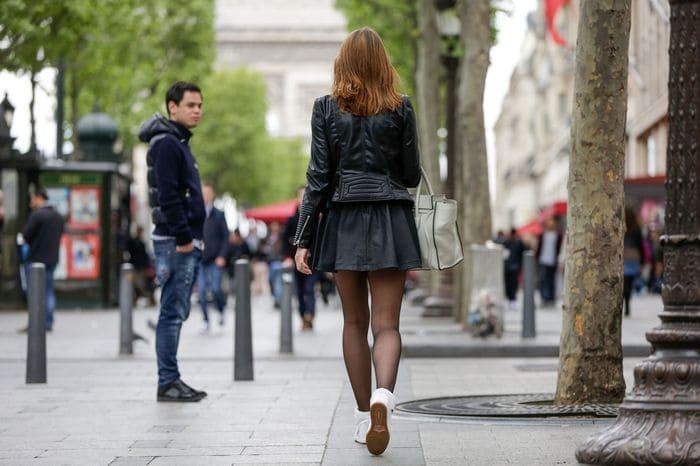 Femme qui marche dans la rue avec un dragueur